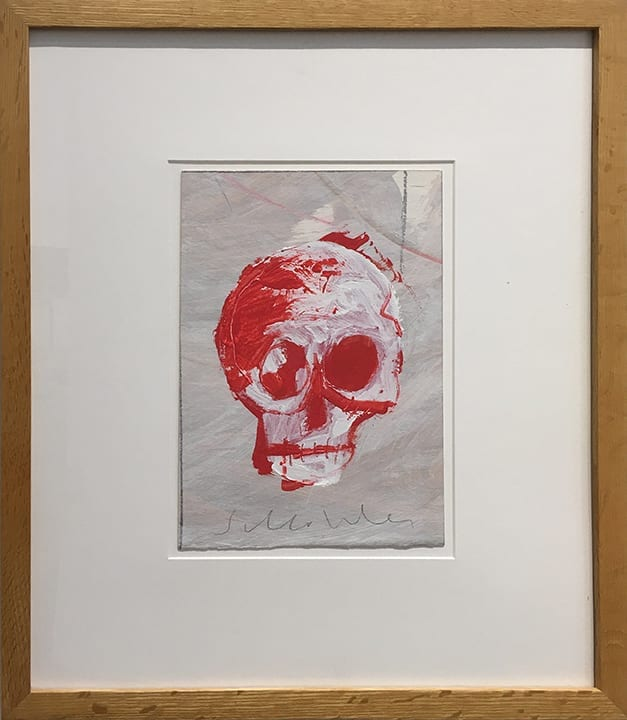 Drawing of red and white skull on gray paper